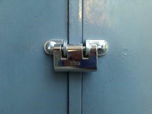 Un candado con 2 vástagos de cierre para usar en puertas y portones de dos batientes, porque se puede dejar enganchado a una de las dos hojas.