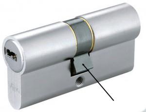 La flecha indica una leva DIN de forma cuadrada y que, con la llave extraída, sobresale del cuerpo del cilindro (normalmente con un ángulo de 30°), ofreciendo resistencia si se intenta forzar el cilindro fuera de su alojamiento.