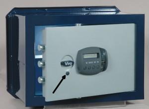 La flecha indica la tapa protectora de la cerradura de seguridad que se puede utilizar para abrir la caja fuerte si las pilas se agotan.