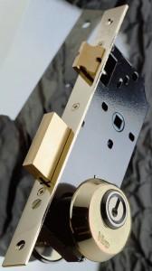 Escudo de seguridad montado en una cerradura con tornillos pasantes a través de orificios DIN.